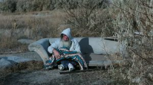 stock-footage-man-outdoor-sofa-homeless-with-blanket-cold-poor-hd-long-hair-beard-sad-and-poor-man-down-on-luck